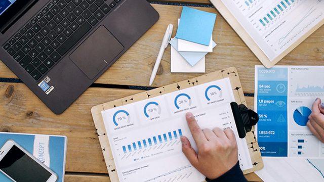 Tisch mit Laptop sowie diversen Ausdrucken zu professionellem Kampagnen Management.