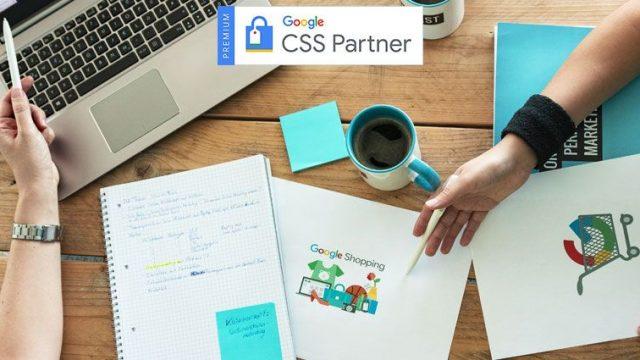 Flatlay eines Tisches mit Laptop, Unterlagen und Kaffeetasse. Zwei Kolleginnen sprechen über die Vorteile eines Google CSS-Partners.