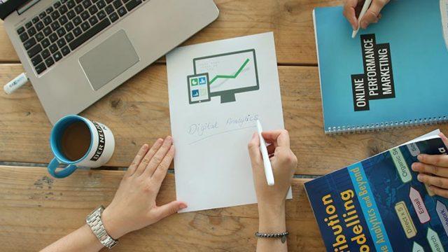 Tisch mit einem Laptop, Stiften und Zetteln zu Google Analytics Alerts.